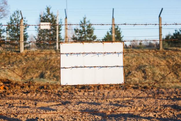 La clôture de barbelés protège la zone dangereuse. panneau blanc Photo Premium