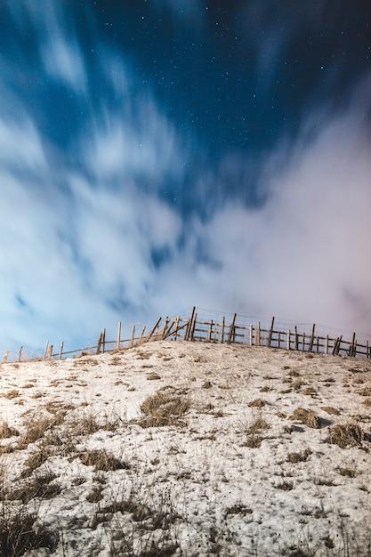 Clôture En Bois Brun Sur Du Sable Brun Sous Le Ciel Bleu Pendant La Journée Photo gratuit