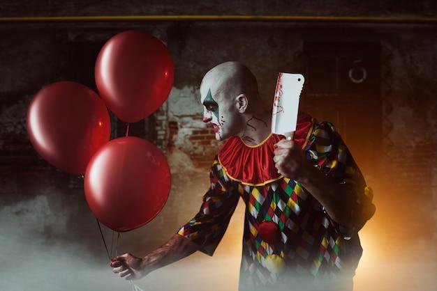Clown Sanglant Effrayant Avec Couperet à Viande Et Ballon à Air Se Faufilant Dans Le Sous-sol, Horreur. Homme Avec Du Maquillage En Costume De Carnaval, Fou Maniaque Photo Premium