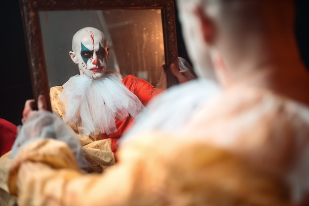 Clown Sanglant Effrayé Regardant Le Miroir Photo Premium
