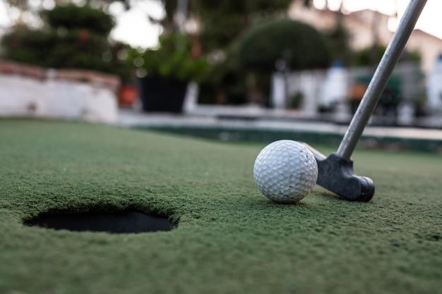 Club de golf, balle de golf et trou dans un terrain de minigolf Photo Premium
