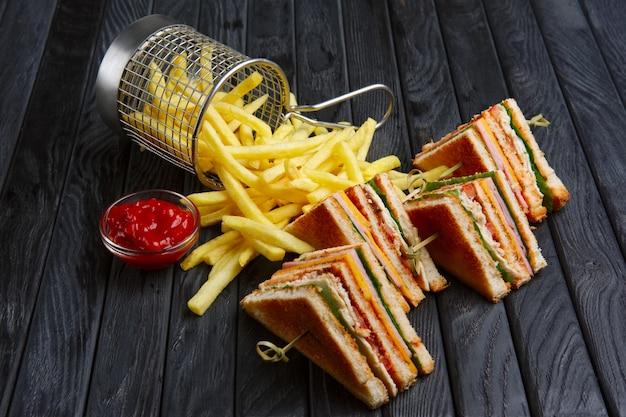 Club-sandwich avec des frites dans un panier en métal Photo Premium