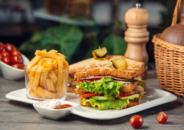 Club sandwich avec laitue, tomate, concombre, poitrine de dinde, frites Photo gratuit