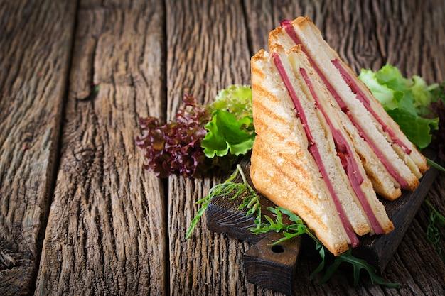 Club sandwich - panini au jambon et fromage sur fond en bois. nourriture de pique-nique. Photo Premium