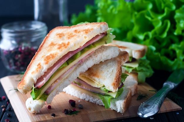 Club sandwich avec une salade sur une plaque de bois Photo Premium