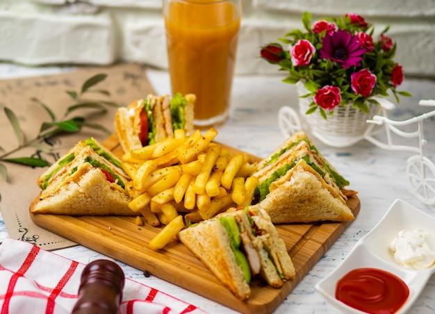 Club sandwich servi avec frites et boisson gazeuse, mayonnaise, ketchup Photo gratuit
