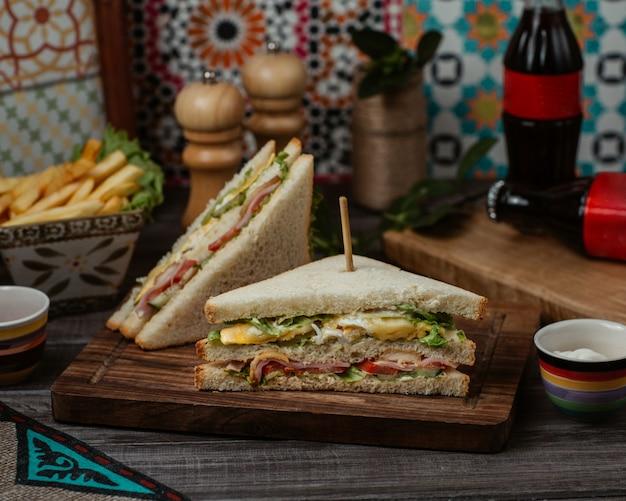 Club sandwichs avec de la verdure et du fromage cheddar à l'intérieur de pain grillé blanc Photo gratuit