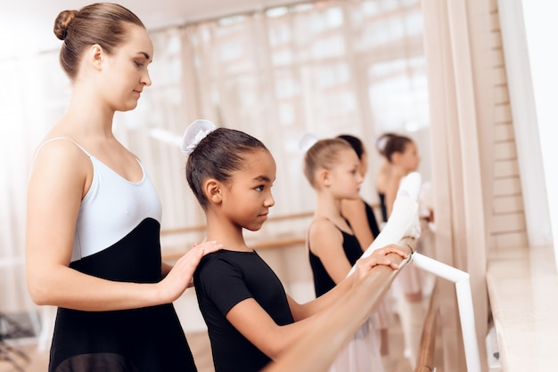Coach aide les petites filles à s'entraîner en classe. Photo Premium