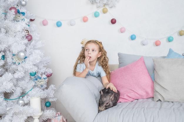 Cochon, symbole de la chance et du calendrier du nouvel an chinois 2019. une drôle de fille s'étonne du bébé mini-cochon sur le canapé près de l'arbre de noël avec des cadeaux, symbole du nouvel an 2019 Photo Premium