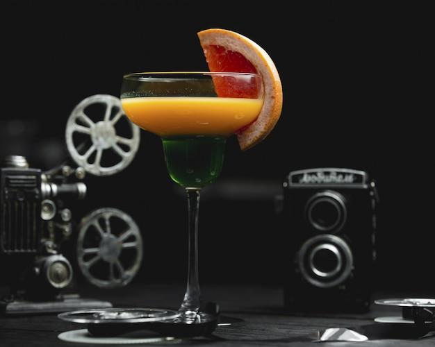Cocktail alcool de pamplemousse avec une tranche de fruit Photo gratuit