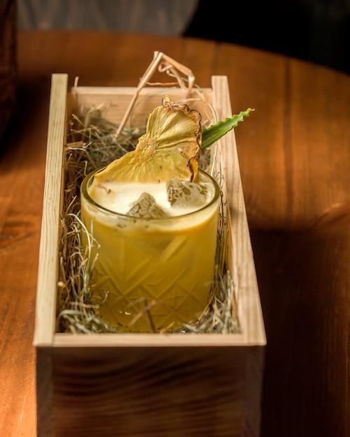 Cocktail d'ananas avec glace et ananas séchés servir dans une boîte en bois avec fourrage Photo gratuit