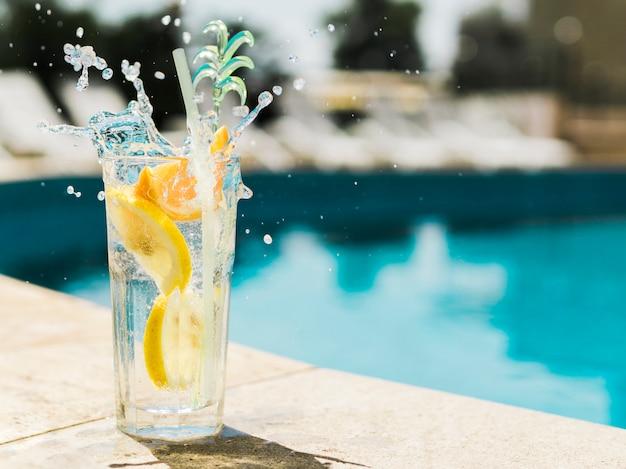 Cocktail au citron éclaboussant près de la piscine Photo gratuit