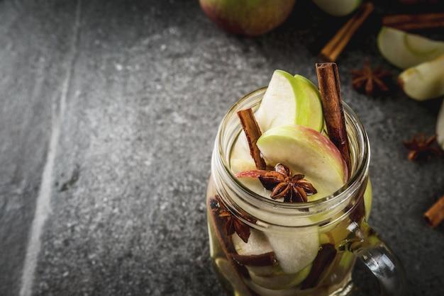 Cocktail D'automne. Infusion Diététique Infusée D'eau Aux Pommes Et épices Anis, Cannelle. Cocktail D'alcool Au Cidre De Pomme. En Pot De Maçon Sur Une Table En Pierre Noire. Fond Photo Premium