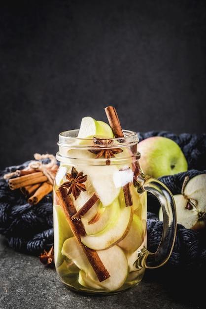 Cocktail D'automne. Infusion Diététique Infusée D'eau Aux Pommes Et épices Anis, Cannelle. Cocktail D'alcool Au Cidre De Pomme. En Pot De Maçon Sur Une Table En Pierre Noire. Photo Premium