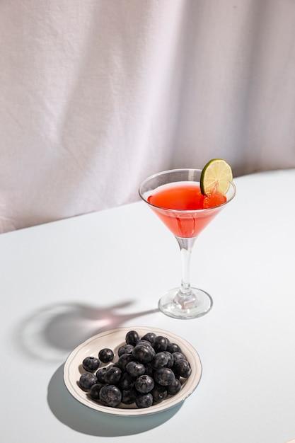 Cocktail avec des baies bleues sur plaque sur fond blanc Photo gratuit