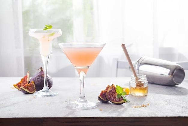 Cocktail bellini à la pêche et aux figues, miel sur fond clair au-dessus des fenêtres, espace copie Photo Premium
