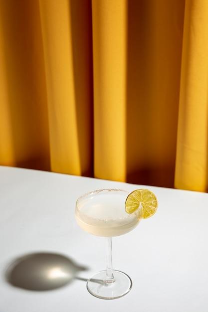 Cocktail de citron vert dans une soucoupe de champagne sur un bureau blanc contre un rideau jaune Photo gratuit
