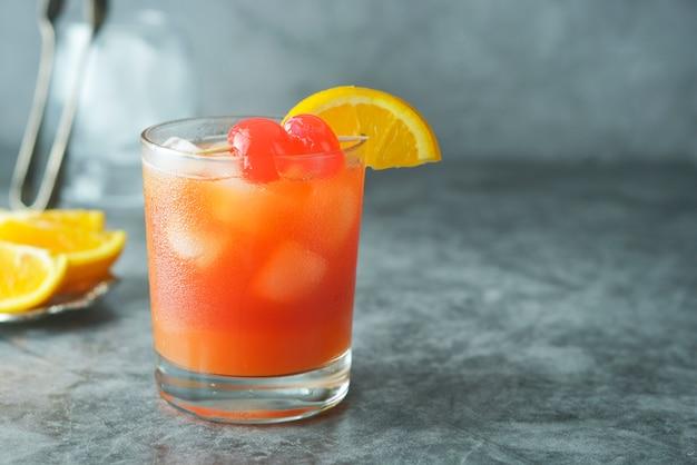 Cocktail d'été. jus d'orange à la menthe, sirop, tranches de fruits et cerise avec glace. Photo Premium