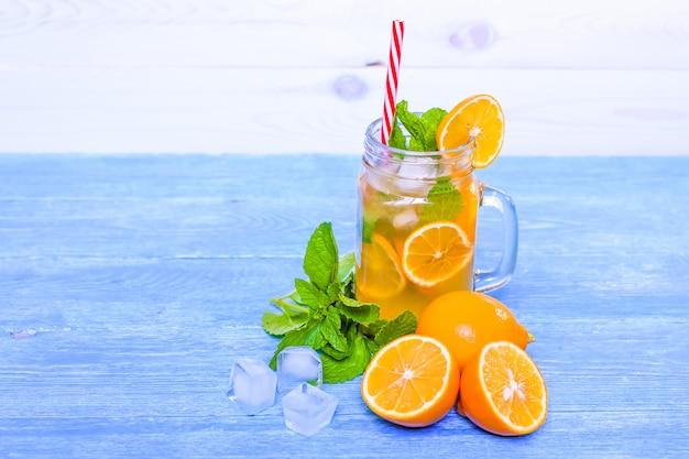 Cocktail d'été mojito à la menthe, jus de citron vert, eau gazéifiée et glace sur une table en bois blanche bleue. Photo Premium