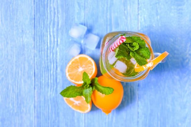 Cocktail d'été mojito à la menthe, jus de citron vert, eau gazeuse et glace sur une table en bois blanche bleue. Photo Premium