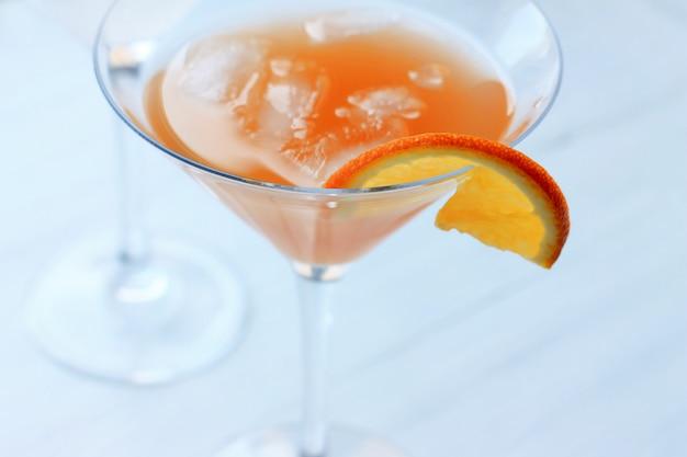 Cocktail avec de la glace dans un verre au bord d'un verre de vue de dessus de fond orange clair Photo Premium