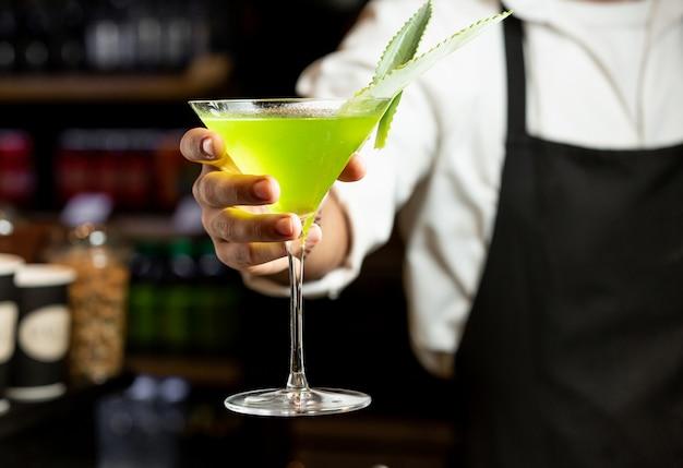 Cocktail jaune dans la main du barman Photo gratuit