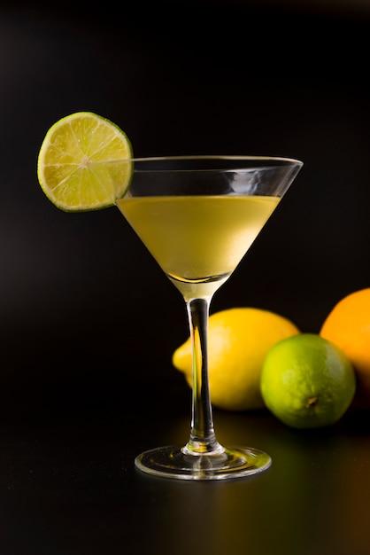Cocktail jaune avec une tranche de citron et au fond un citron Photo Premium