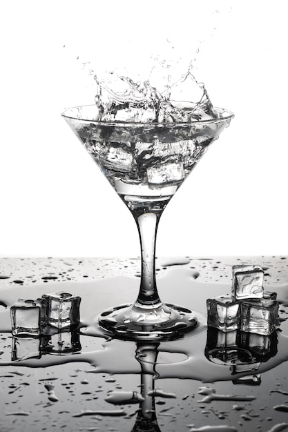 Cocktail de martini avec de la glace dans un verre. splash et glaçons. Photo Premium