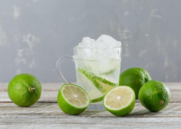 Cocktail Mojito Glacé Dans Une Tasse Avec Vue De Côté De Limes Sur Fond De Bois Et De Plâtre Photo gratuit