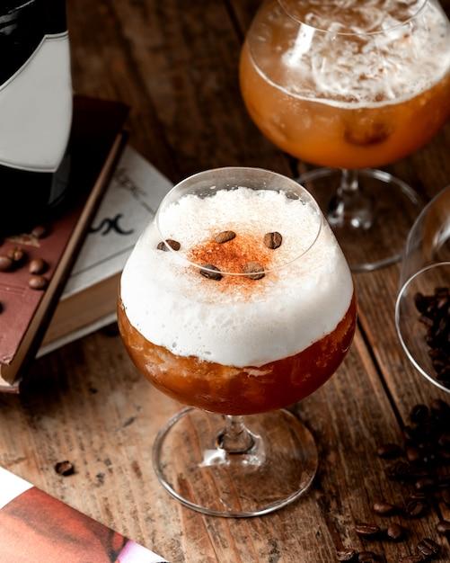 Cocktail mousseux à la cannelle garni de grains de café et de cannelle en poudre Photo gratuit