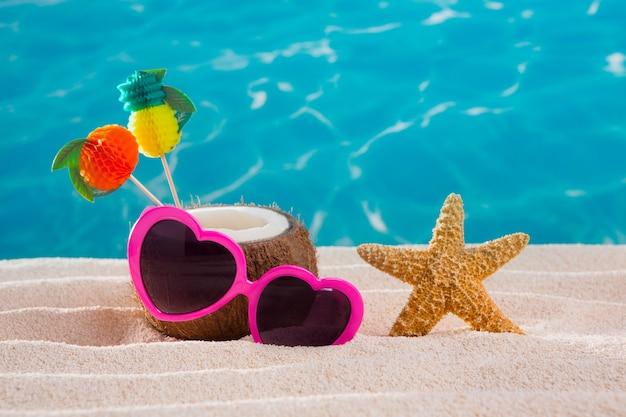 Cocktail de noix de coco sur des lunettes de soleil de coeur de plage de sable tropicale Photo Premium
