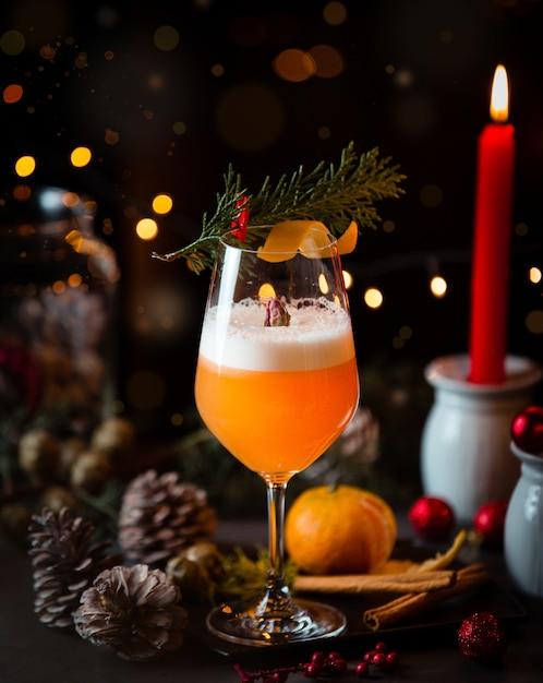 Cocktail Orange Avec Des Cônes De Noël, Des Lumières Et Une Bougie Rouge. Photo gratuit