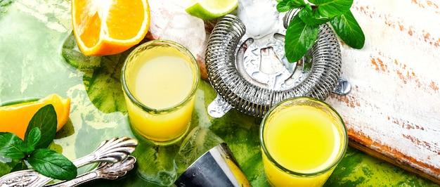 Cocktail à l'orange avec tranche de citron vert et glace.verre de boisson à l'orange Photo Premium