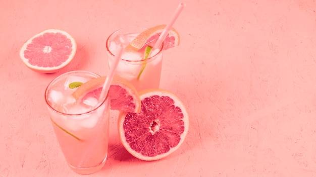Cocktail de pamplemousses avec des tranches de fruits et des glaçons sur fond texturé corail Photo gratuit