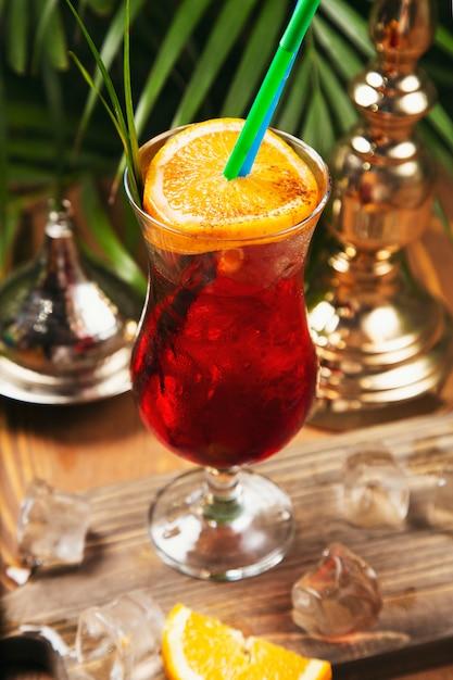 Cocktail rouge avec une tranche d'orange sur une table de cuisine en bois Photo gratuit