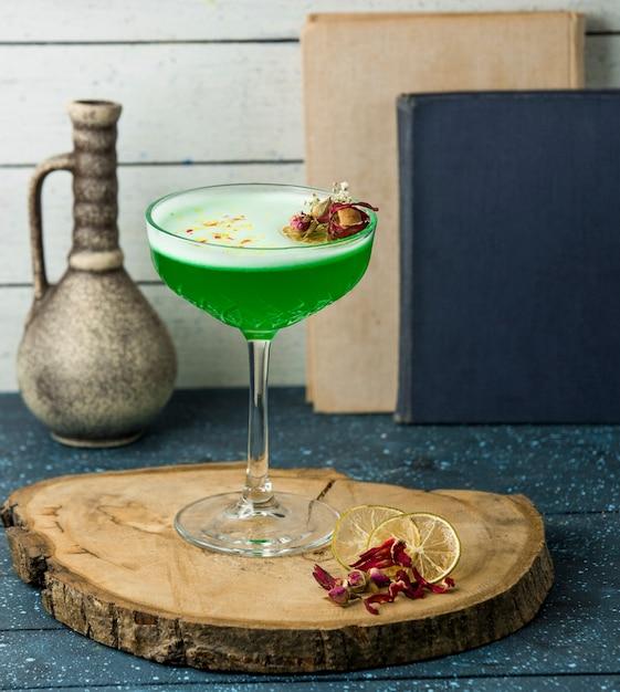 Cocktail vert avec des fleurs sur la table Photo gratuit