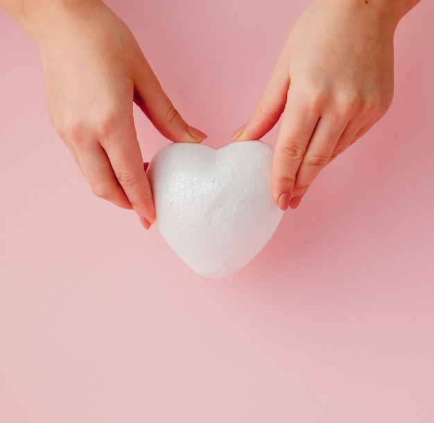 Coeur D'amour Vide Blanc Dans Les Mains Sur L'espace Rose Photo Premium