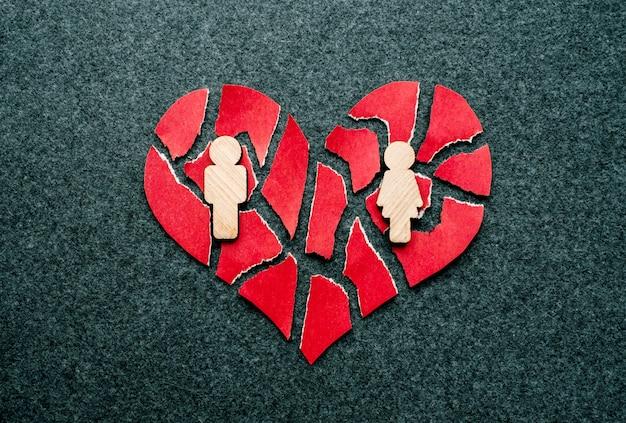 Coeur brisé de papier rouge avec des figures en bois de l'homme et de la femme Photo Premium