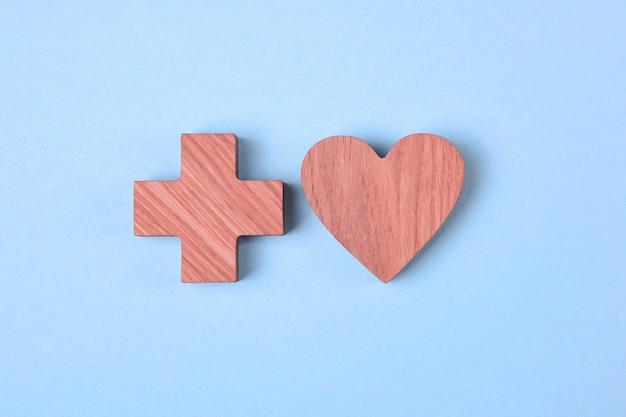 Coeur Et Croix, Icônes En Bois Teintées D'une Tache Rose Sur Fond Bleu Pâle Photo Premium