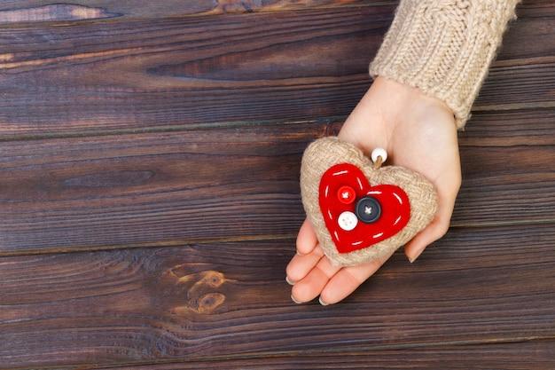 Avec coeur dans les mains sur fond en bois. concept de la saint-valentin Photo Premium