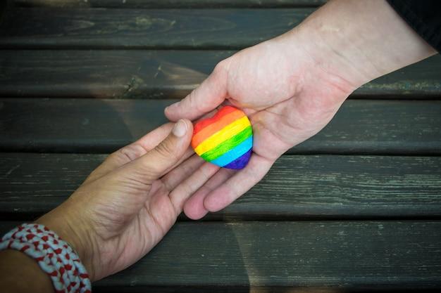 Coeur décoratif avec des rayures arc-en-ciel dans les mains des hommes. drapeau de fierté lgbt, amour homosexuel, concept des droits de l'homme. Photo Premium