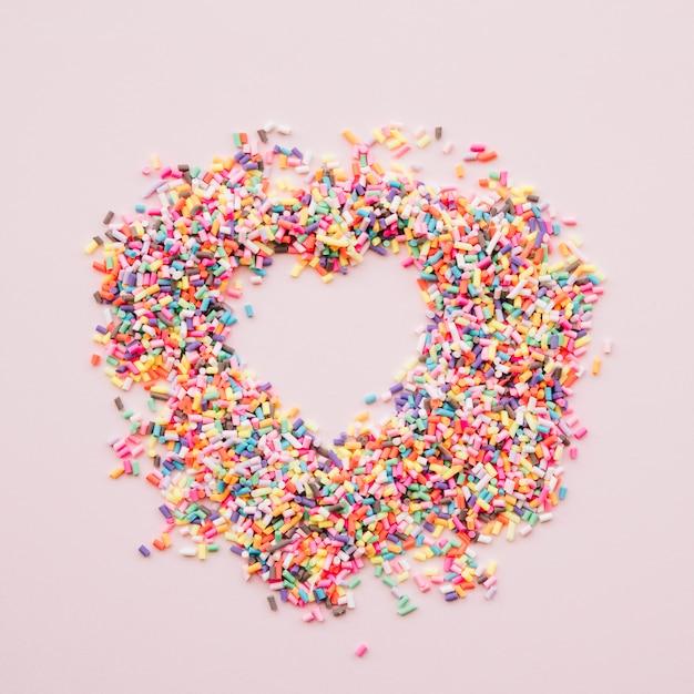 Coeur entre différents bonbons colorés Photo gratuit