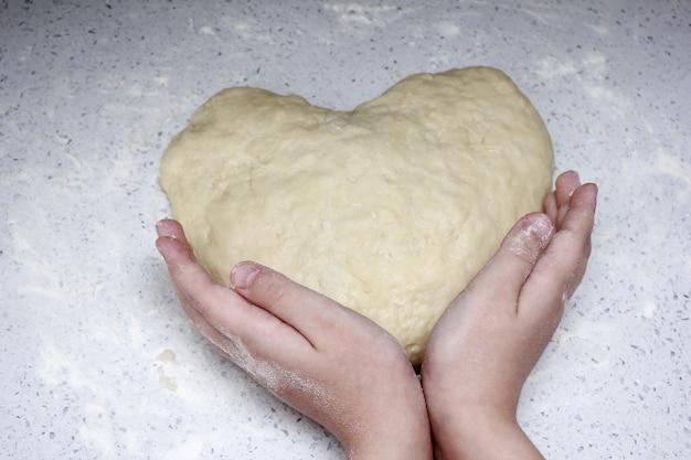 Un Cœur Fait De Pâte Est Tenu Par Les Mains Des Enfants. Photo Premium