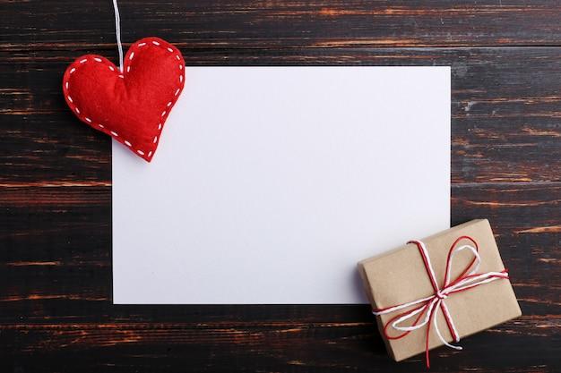 Coeur en feutre rouge fait main et cadeau, à côté de papier blanc, sur une table en bois Photo Premium
