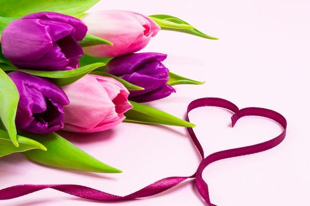 Coeur en forme de ruban violet et bouquet de tulipes violettes et roses sur fond rose pâle Photo Premium