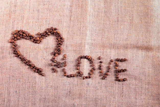 Coeur Avec Des Grains De Café Torréfiés Sur Le Fond De Toile De Jute Photo Premium