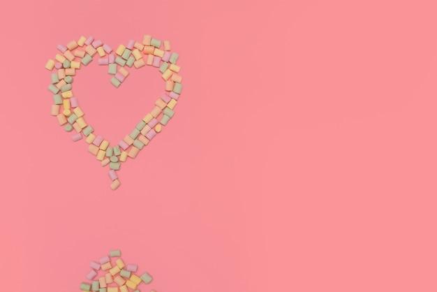 Cœur de guimauves multicolores isolé sur fond rose Photo Premium