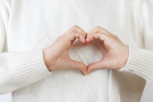Coeur avec les mains. la jeune fille se tient la main dans la forme du coeur Photo Premium