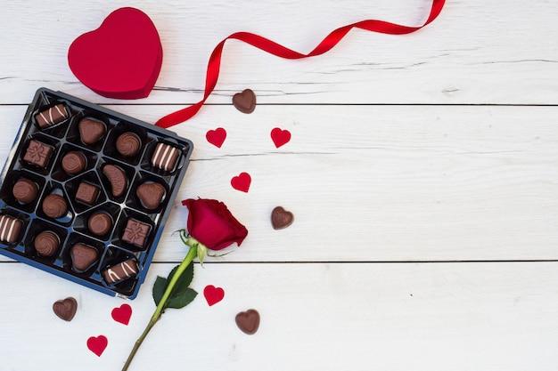 Coeur d'ornement près de ruban, fleur et bonbons Photo gratuit