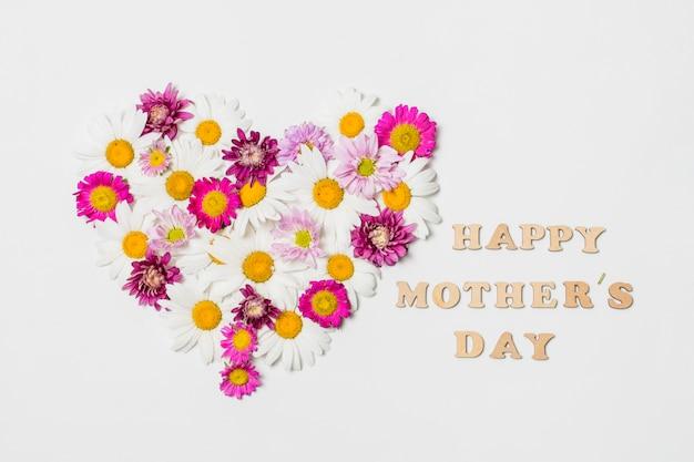Cœur ornemental de fleurs aux couleurs vives près du titre de la fête des mères Photo gratuit